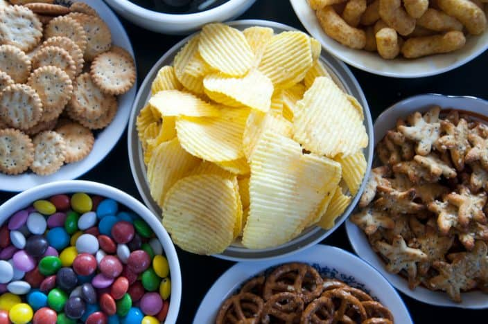 an assortment of snacks in different bowls including MnMs, pretzels, crackers, potato chips and cheese puffs
