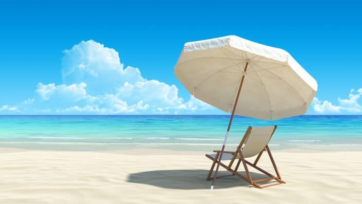 picture of a beach chair on the sand under the umbrella which is providing it shade, under a blue sky with clouds, also there is the sea in the background with blue water.