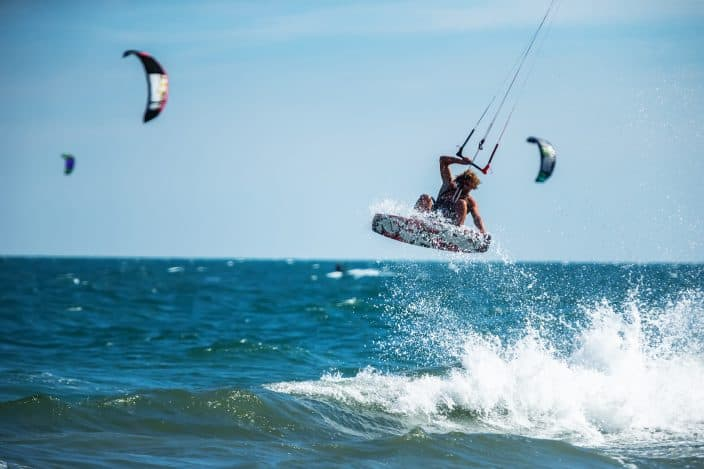 a man kite surfing in the ocean with blue waters and a blue sky, the perfect beach day activity