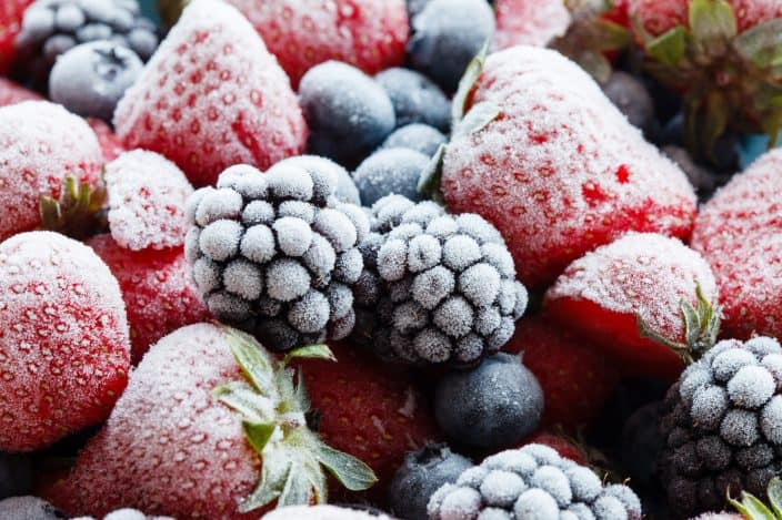 a close up of frozen blackberries, strawberries, and blueberries