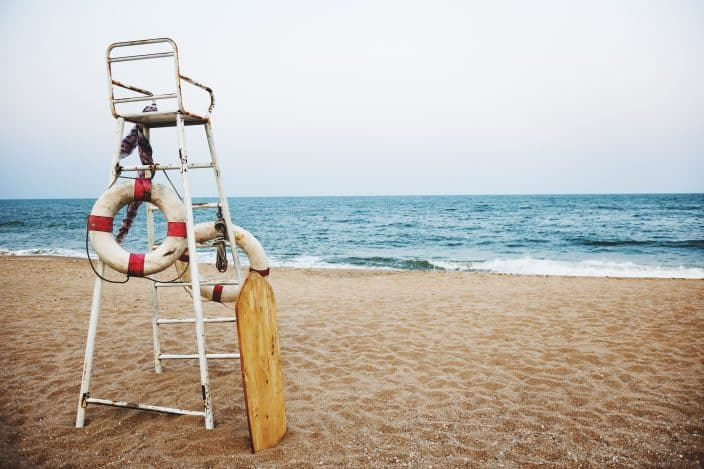 view of the tall lifeguard chair in front of the seashore with golden sand and grey blue skies to represent a useful beach hack