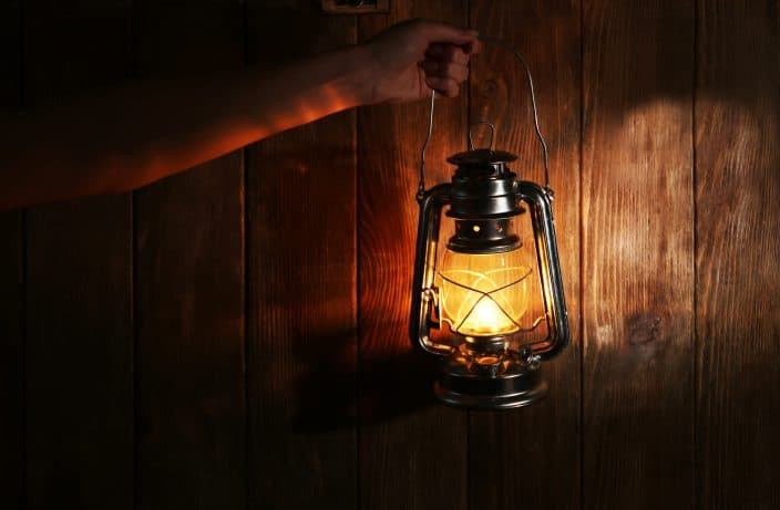 a lit lantern being held up by a hand in front of a wooden background