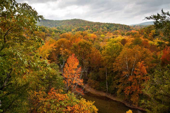 Buffalo National River in Arkansas with orange, red, and yellow leaves on the trees and grey skies, a fall bucket list destination