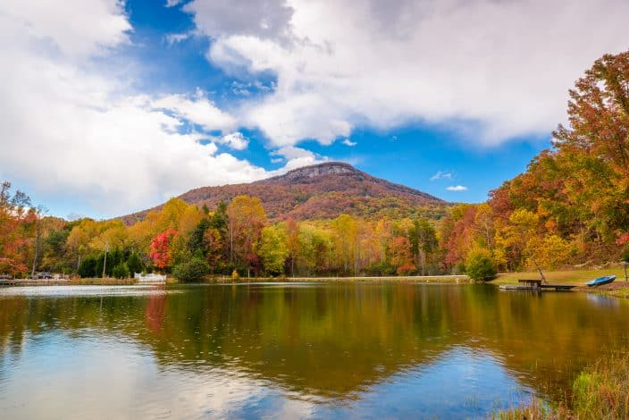 a lake in Georgia with trees on the banks with gold, orange, and red leaves on them, with a mountain in the background with red and orange foliage and bright blue skies with clouds, a fall bucket list destination.