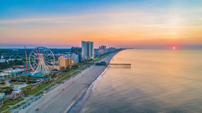 The shoreline in Myrtle Beach during sunset, with blue, pink and orange skies, a Ferris wheel with high rises on the beach and a pier going into the ocean.