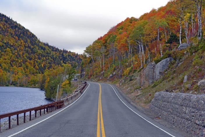 a road running through the mountains during fall, with trees with red, orange, and yellow leaves on the right side. There is a lake on the left with a guardrail against the road, as a representation of a fall road trip