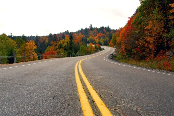 A winding road through the mountains, trees with fall foliage are on either side, an example of what you can see during a fall road trip