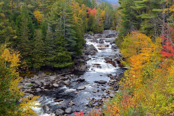 a creek filled with large and small grey rocks, running through the mountains with red, orange, yellow, and green foliage on the trees on either side, as a representation of what you can see during fall road trips