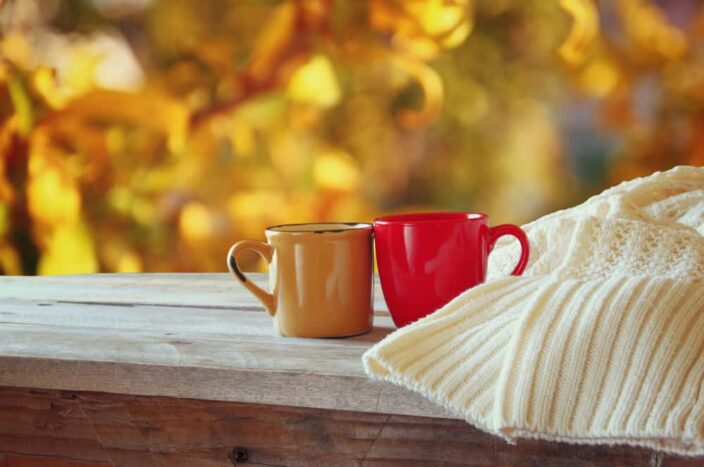 one orange mug and one red mug sitting next to each other on a wooden table with a cream knit sweater next them and fall foliage colors in the background, as a representation of a romantic getaway on a road trip