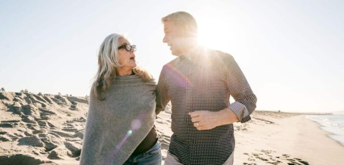 Woman with medium length hair and dark glasses, wearing a grey cover cashmere coverup with jeans while walking on the beach with her male partner wearing a checkered shirt and rolled sleeves making the perfect sunset evening attire to add to your packing list for beach vacation