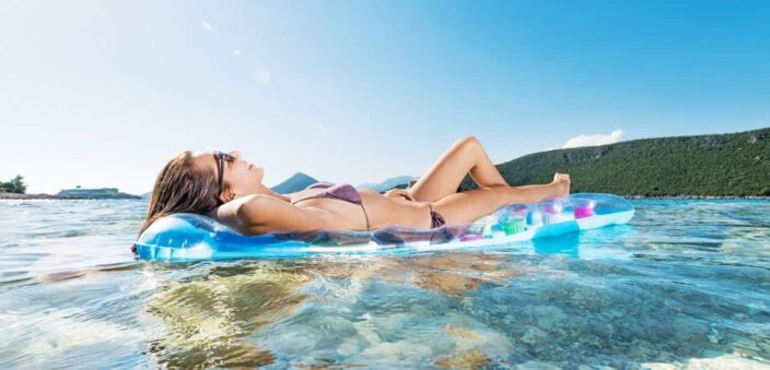 Blue skies, clear water with green mountain in the background and relaxed woman floating on her raft with purple bikini that she brought from her Packing List for Beach Vacation