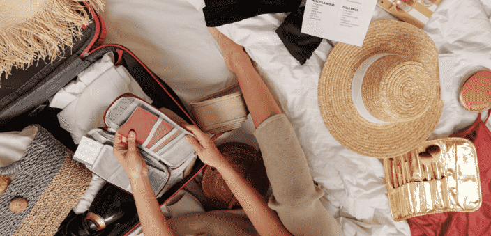 Packing suitcase with items for beach vacation. Wide brimmed hat on bed, passport and itinerary in her hands, makeup kit on bed beside her, packing list for beach vacation printed on bed beside her, suitcase open with clothing  placed inside and grey bag to carry items to the beach with.