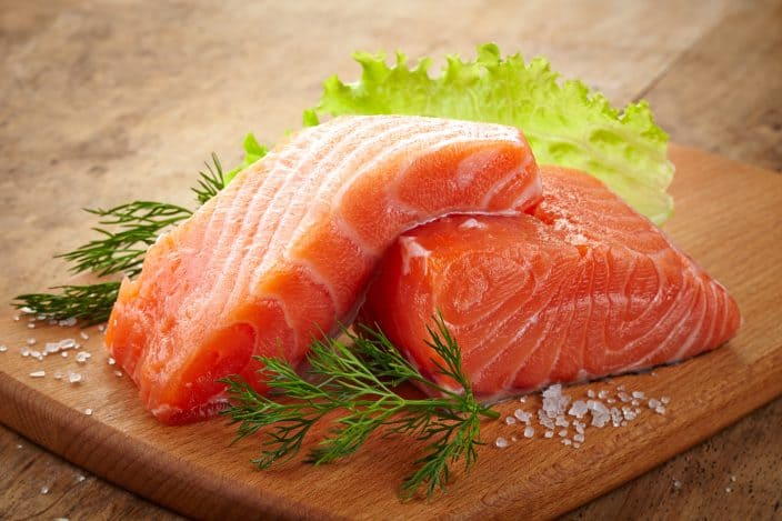 two fresh raw salmon pieces on a wooden cutting board with salt sprinkled and dill and lettuce on a wooden table to use for the making of teriyaki citrus salmon