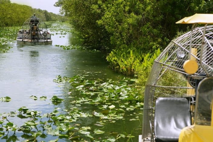 2 airboats in Everglades Florida Big Cypress National Preserve with lily pads on the water, green brush on the sides of the water and grey skies