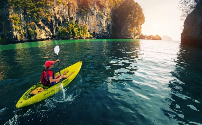 a young lady in a red shirt paddling a yellow kayak in the calm bay with limestone mountains with the sun shining on the water