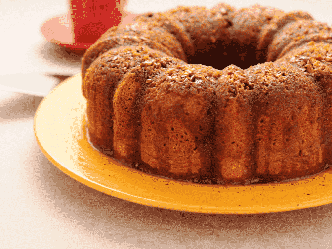 a rum cake sitting on a yellow plate on a beige counter top with a red cup in the background
