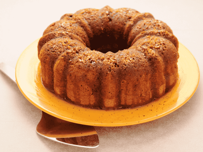 A Caribbean rum cake on a yellow plate on a beige counter top with a silver spatula