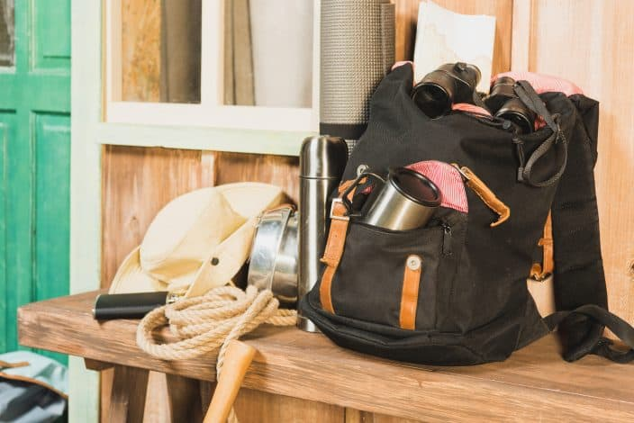a black backpack sitting on a wooden bench with binoculars, a thermos, a rope, and a cowboy hat