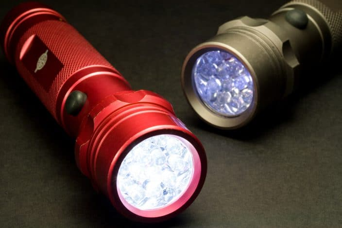a red and a gold flashlight that are on laying on a dark background, to represent an important camping essential