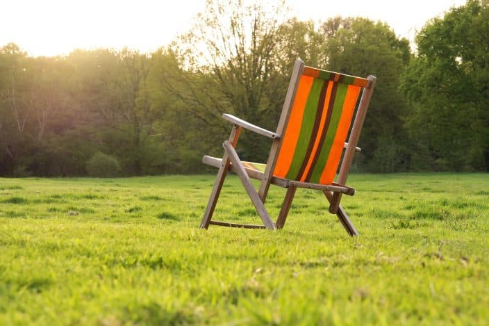 an orange and green striped chair with wooden legs sitting in a green field with trees during sunrise