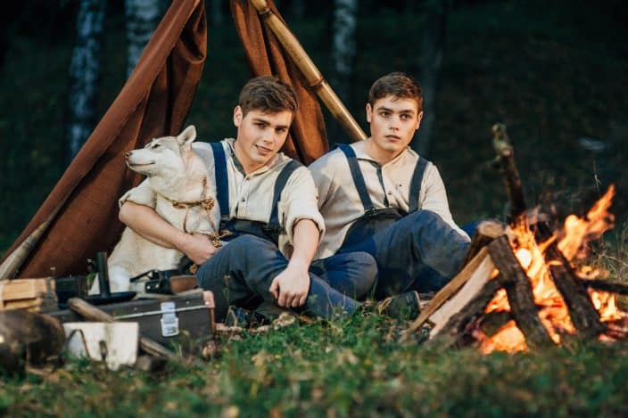two twin brothers in blue jean overalls and beige shirts sitting in front of a campfire and in front of a brown tent with a dog at night