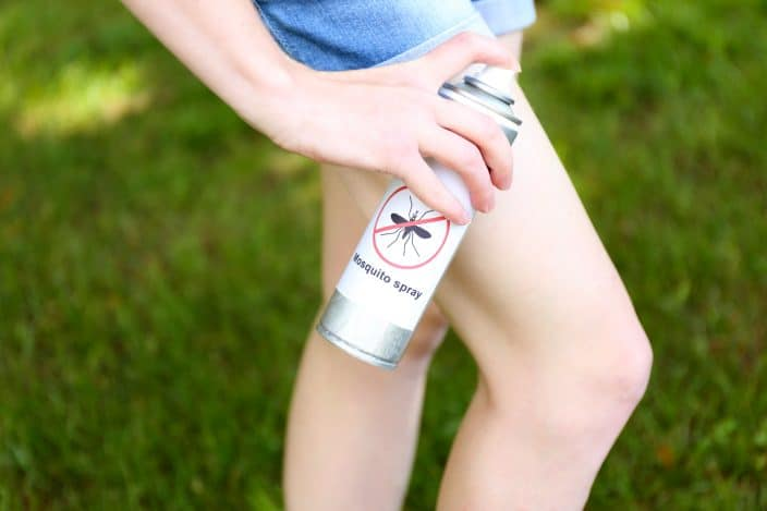 Women in blue jean shorts spraying mosquito repellent, a camping essential, on her knee outside with green grass.