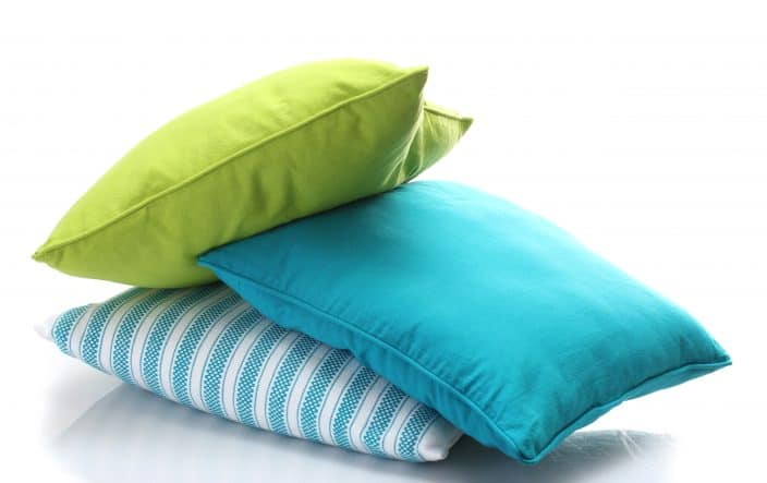 a bright, lime green, bright blue, and blue and white striped pillows on a white background