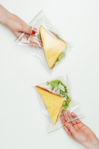 2 Ziploc bags with triangle cut sandwiches with lettuce on them inside of them on a white background. A hand with red nail polish is holding the top bag and another hand is holding the bottom bag.
