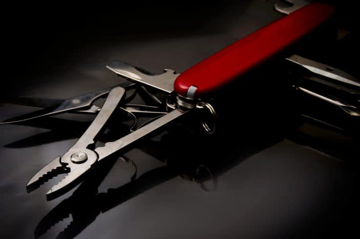 Picture of  red swiss knife with a plain dark background.