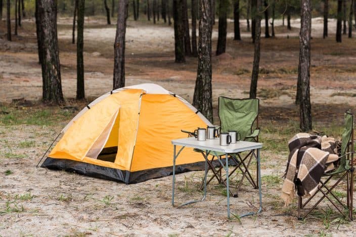 view of the camping site with yellow tent, a table with silver mugs on it,  green chairs, brown ground, and trees in the background.