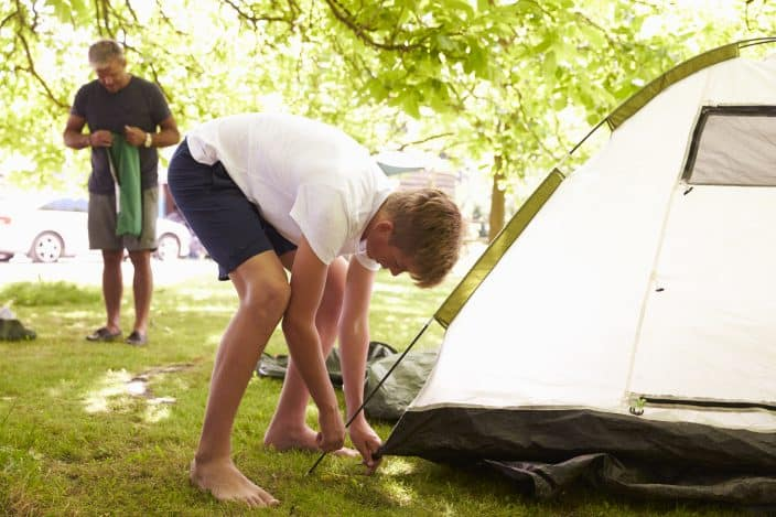 Father And Teenage Son Putting Up a white Tent, on green grass, with trees in the background On Camping Trip