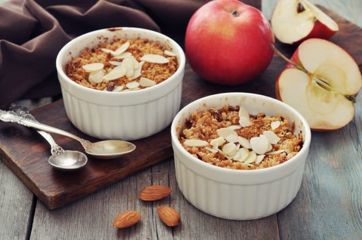 Apple crisp in  2 ceramic molds on a wooden cutting board on a wooden table with fresh apples, silver spoons, and almonds in the foreground.