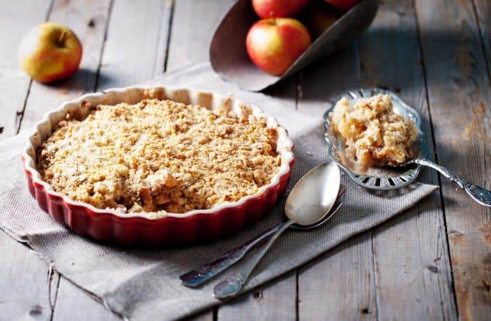 apple crisp in a red pie dish with silver spoons in front with a silver spoon filled with apple crisp on the side on a wooden background with whole apples in the background