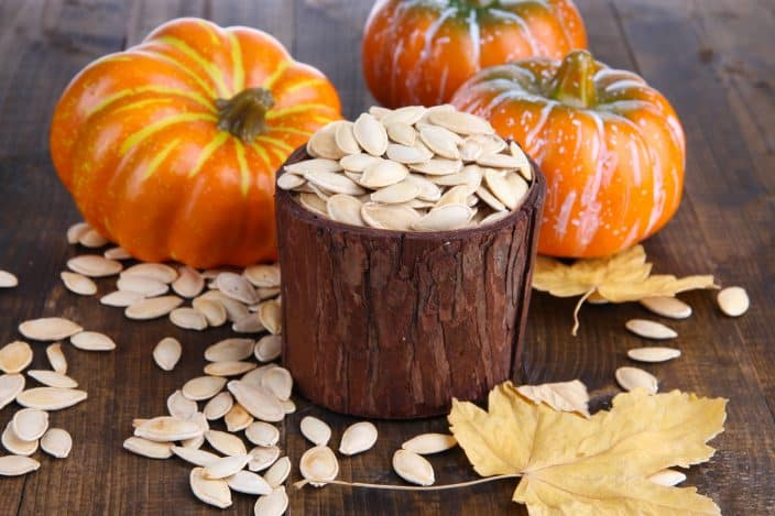 Pumpkin seeds in a wooden pot with orange pumpkins, pumpkin seeds, and maple leaves on the wooden table background