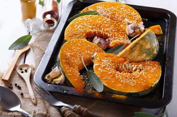 Cut open roasted pumpkin on a black baking sheet topped with white sesame seeds, garlic, and jars of orange and red spices in the background, an example of pumpkin healthy recipes