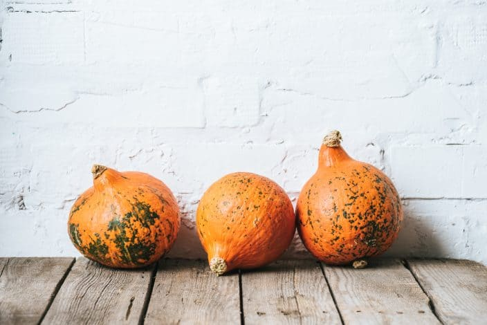whole orange pumpkins with green veining with a white brick background and wooden flooring