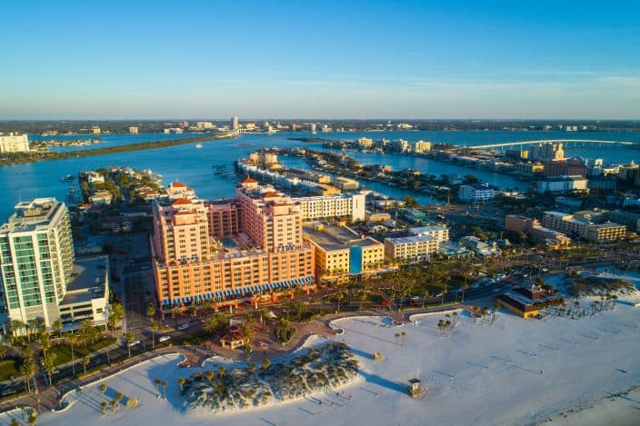 Aerial image of Clearwater Beach Florida, a romantic getaway weekend destination, with resorts and condominium apartments on the shoreline, bright blue skies and blue waters with bridges in the background.