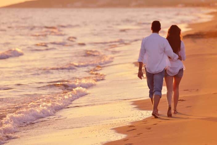 a man and a woman in white button down shirts and jeans walking on the beach during sunset to represent a romantic getaway weekend at the beach