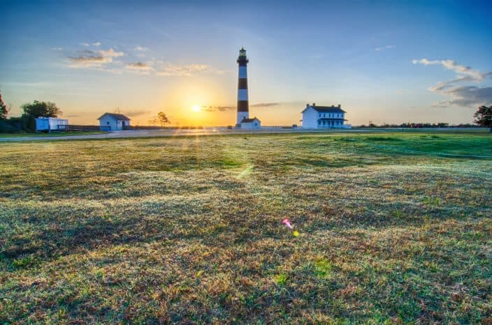 A large piece of farmland during sunrise with the Bodie Island Lighthouse and a white house next to it and a white shed on the left. The grass has dew on it and the sky is blue with an orange sun