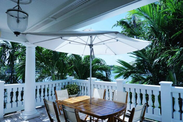 The Pillars, Fort Lauderdale balcony with stone railing, a white umbrella over a wooden table with white and wood woven chairs and a view of large green palm trees.