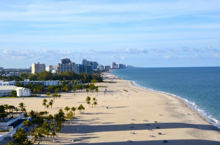 An aerial view of Fort Lauderdale beach with blue ocean, skies and beach with green palm trees and sky scrapers in the distance.