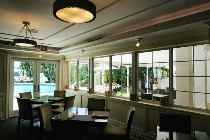 The inside dining area at The Secret Garden with a view of the pool with dark wooden tables, fabric chairs, low, ambient lighting