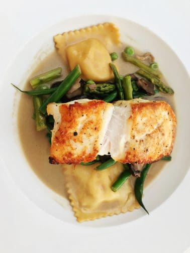 a piece of white fish with orange seasoning on top of asparagus, green beans, and ravioli in a cream sauce.