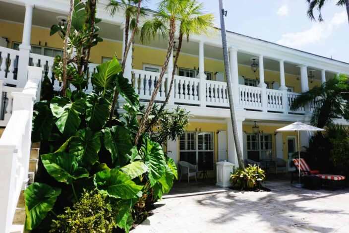 A view of The Pillars Hotel in Fort Lauderdale exterior- a yellow boutique hotel with white stone railings wrapping around the second floor balcony, a staircase with a white stone railing and large tropical palms and greenery growing around the outside of the hotel