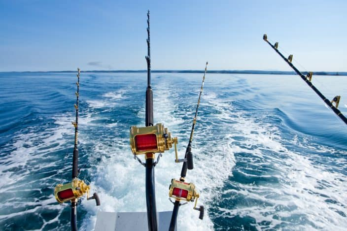 the of 4 deep sea fishing poles cast off the back of a fishing boat with blue water in the background and bright blue skies