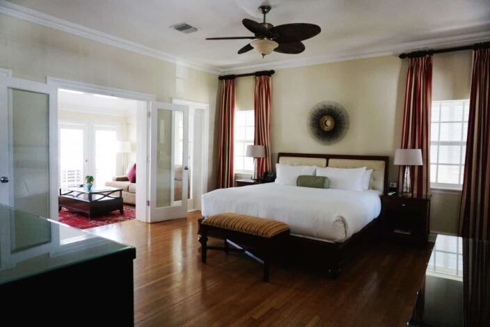 a view of a suite at The Pillars, Fort Lauderdale with mahogany wood floors, bed frame and side tables. The walls are a light yellow beige color, with double doors leading to the living area of the suite with a red rug and a beige couch, and wood table.