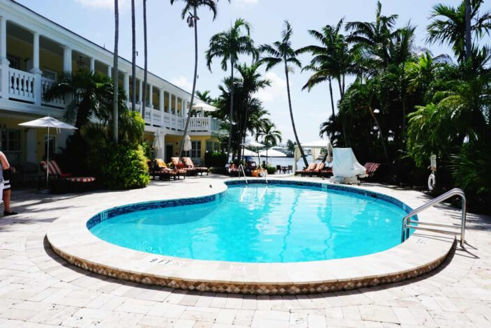 a view of the pool with cobble stone paving at The Pillars Hotel in Fort Lauderdale with many green palm trees, red and white striped lounge chairs, and a view of blue skies and the waterfront in the background