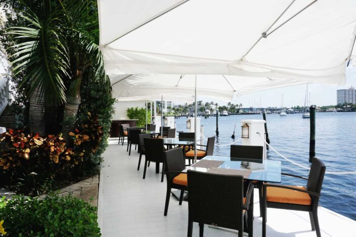 an image of the view at the Secret Garden restaurant at The Pillars hotel featuring dining chairs and tables along the Intercoastal Waterway with white umbrellas above and greenery and palms on the side