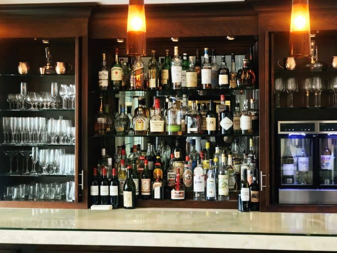 The Pillars, Fort Lauderdale bar with many bottles of alcohol lined up against a mirrored wooden cabinet with alcohol glasses on the left side and more glasses on the right with a wine cooler