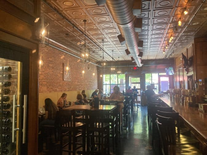 the interior at Clear Sky on Cleveland, with wood and copper interiors, bar tables and chairs and people enjoying food, an example of things to do in Clearwater Beach